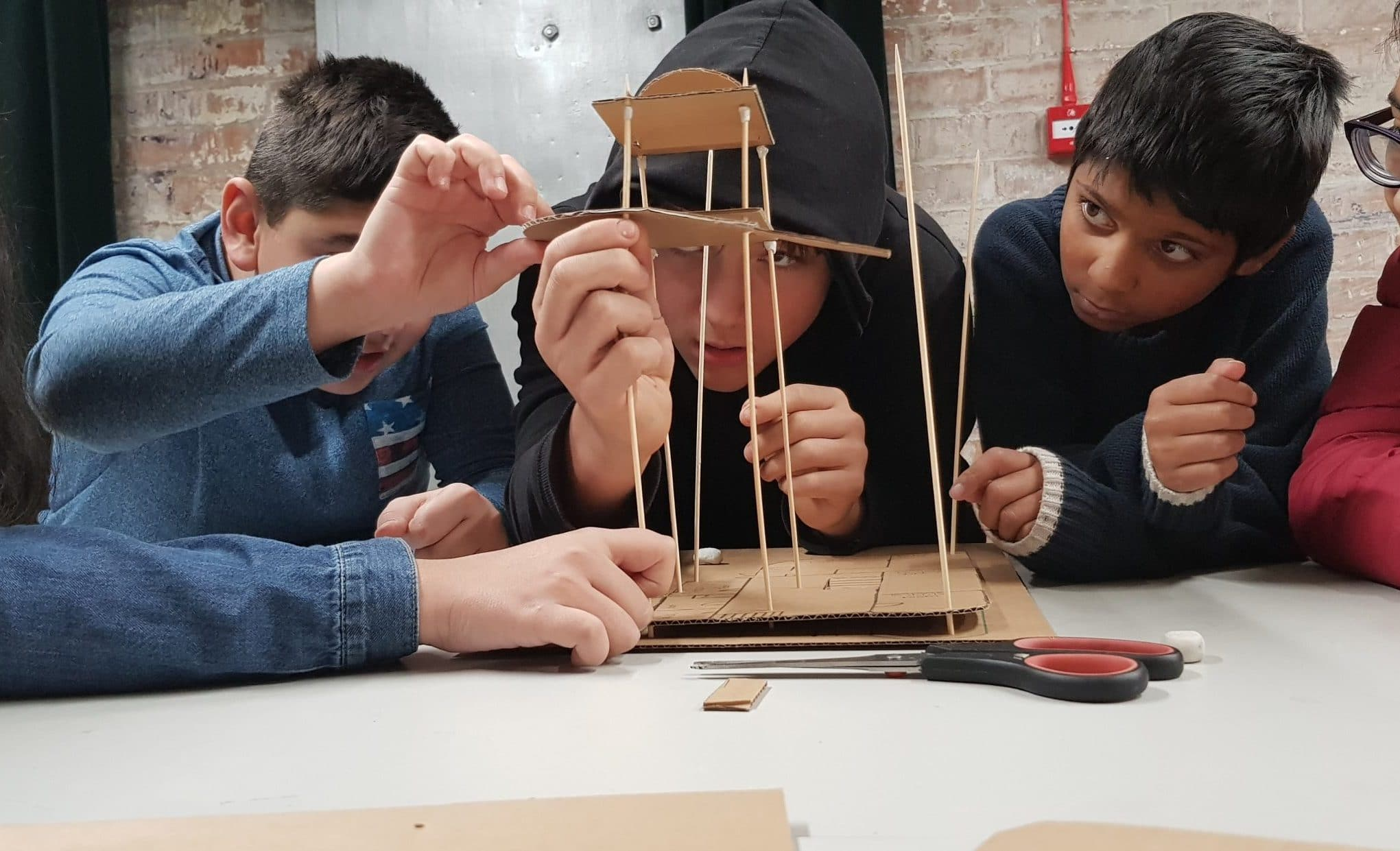 Five children sit around a table, focusing on artwork in front of them made out of wooden skewers and cardboard.